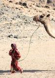 Το βεδουίνο κορίτσι στο εθνικό φόρεμα καθοδηγεί την καμήλα στην έρημο Στοκ φωτογραφίες με δικαίωμα ελεύθερης χρήσης