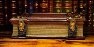 Το βιβλίο με τις επιχρυσωμένες σελίδες και οι αγκράφες καθορίζουν στον ξύλινο πίνακα στοκ εικόνες