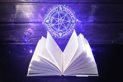 Το βιβλίο στον πίνακα έρχεται έξω ελαφρύ και μαγικό σημάδι Στοκ εικόνες με δικαίωμα ελεύθερης χρήσης