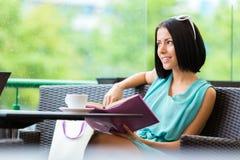 Το βιβλίο ανάγνωσης κοριτσιών πίνει το τσάι στο φραγμό Στοκ φωτογραφίες με δικαίωμα ελεύθερης χρήσης