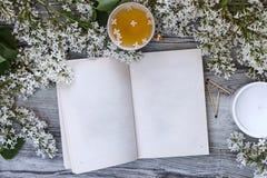 Το βιβλίο με τις κενές σελίδες περιβάλλεται από τα λουλούδια της άσπρης πασχαλιάς, μια κούπα του τσαγιού με τα ιώδη πέταλα σε ένα Στοκ Φωτογραφία