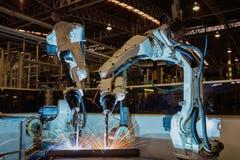 Το βιομηχανικό ρομπότ στο εργοστάσιο αυτοκινήτων ενώνει στενά το μέρος συνελεύσεων Στοκ Εικόνες