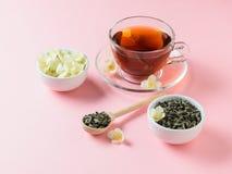 Το βοτανικό τσάι, μέλι, Jasmine ανθίζει και ένα ξύλινο κουτάλι σε έναν ρόδινο πίνακα Η σύνθεση του χρώματος κρητιδογραφιών προγευ Στοκ Φωτογραφία