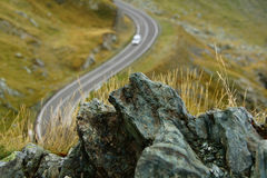 Το βουνό λικνίζει το πρώτο πλάνο με το αυτοκίνητο στο backgound και το ρηχό βάθος του τομέα Στοκ Εικόνες