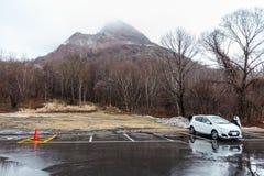 Το βουνό με το χιόνι και την ομίχλη στην κορυφή και τα δέντρα κατωτέρω στο carpark Noboribetsu αντέχουν το πάρκο στο Hokkaido, Ια Στοκ Φωτογραφία