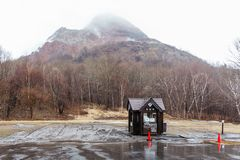 Το βουνό με το χιόνι και την ομίχλη στην κορυφή, τα δέντρα και το σπίτι φρουράς κατωτέρω στο carpark Noboribetsu αντέχουν το πάρκ Στοκ φωτογραφίες με δικαίωμα ελεύθερης χρήσης