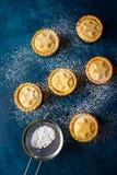 Το βρετανικό σπίτι ζύμης Χριστουγέννων που ψήνεται κονιοποιημένος κομματιάζει τις πίτες με την πλήρωση μαρμελάδας βερίκοκων καρυδ στοκ εικόνα