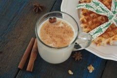 Το γάλα με την κανέλα σε μια διαφανή κούπα, βάφλες, κέικ, έδεσε με την κορδέλλα Χριστουγέννων Στοκ Φωτογραφίες