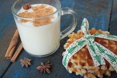 Το γάλα με την κανέλα σε μια διαφανή κούπα, βάφλες, κέικ, έδεσε με την κορδέλλα Χριστουγέννων, Στοκ Εικόνα