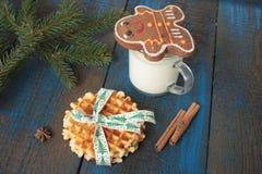 Το γάλα με την κανέλα σε μια διαφανή κούπα, βάφλες, κέικ, έδεσε με την κορδέλλα Χριστουγέννων, γλυκάνισο Στοκ εικόνα με δικαίωμα ελεύθερης χρήσης