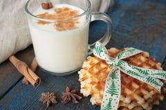 Το γάλα με την κανέλα σε μια διαφανή κούπα, βάφλες, κέικ, έδεσε με την κορδέλλα Χριστουγέννων, γλυκάνισο Στοκ φωτογραφία με δικαίωμα ελεύθερης χρήσης