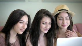 Το γέλιο και τα χαμόγελα της γοητείας των κοριτσιών εξετάζουν την οθόνη lap-top Έχετε τη διασκέδαση από κοινού απόθεμα βίντεο