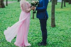Το γαμήλιο ζεύγος κρατά τη γαμήλια ανθοδέσμη στα χέρια Γυναίκα Curvy στο ρόδινο φόρεμα βραδιού δαντελλών Γαμήλια ανθοδέσμη με τα  στοκ εικόνα με δικαίωμα ελεύθερης χρήσης