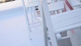 Το γαμήλιο ντεκόρ στις καρέκλες, τις κορδέλλες και το λουλούδι στις άσπρες καρέκλες, κορδέλλες σατέν αναπτύσσεται στον αέρα απόθεμα βίντεο