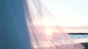Το γαμήλιο φόρεμα κυματίζει στον αέρα στη θάλασσα στο ηλιοβασίλεμα το καλοκαίρι Διαφανές πλέγμα πέπλων από τις πυρακτώσεις φουστώ φιλμ μικρού μήκους