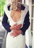Το γαμήλιο κομψό ζεύγος που αγκαλιάζει, δένει το νυφικό φόρεμα στοκ φωτογραφία