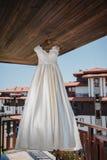 Το γαμήλιο νυφικό φόρεμα κρεμά έξω από το ξενοδοχείο Στοκ φωτογραφία με δικαίωμα ελεύθερης χρήσης