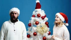 Το γενειοφόρα άτομο και το κορίτσι στα νέα καπέλα έτους παρουσιάζουν διαφορετικές συγκινήσεις κοντά στο χριστουγεννιάτικο δέντρο  απόθεμα βίντεο