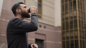 Το γενειοφόρο άτομο ελέγχει το έξυπνο ρολόι του που στέκεται με ένα φλιτζάνι του καφέ απόθεμα βίντεο