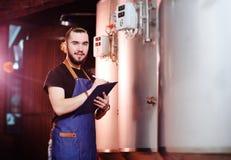 Το γενειοφόρο άτομο ζυθοποιών σε ένα υπόβαθρο της μπύρας τοποθετεί σε δεξαμενή και ένα ζυθοποιείο κάνοντας τις σημειώσεις σε μια  στοκ φωτογραφίες