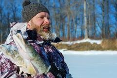Το γενειοφόρο άτομο κρατά τα παγωμένα ψάρια μετά από τον επιτυχή χειμώνα αλιεύοντας στην κρύα ηλιόλουστη ημέρα Στοκ Εικόνες
