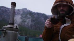 Το γενειοφόρο άτομο πίνει το τσάι στο στρατόπεδο τουριστών στην κοιλάδα βουνών Ταξίδι στην κρύα εποχή ως τρόπο ζωής αργός φιλμ μικρού μήκους