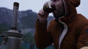 Το γενειοφόρο άτομο πίνει το τσάι στο στρατόπεδο τουριστών στην κοιλάδα βουνών Ταξίδι στην κρύα εποχή ως τρόπο ζωής αργός απόθεμα βίντεο