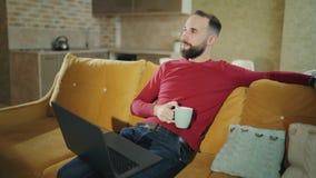 Το γενειοφόρο άτομο που έχει τον καφέ ή το τσάι σταματά χρησιμοποιώντας το lap-top ενώ στο σπίτι 4k μήκος σε πόδηα απόθεμα βίντεο