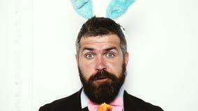 Το γενειοφόρο άτομο που φορά ένα κοστούμι και με τα αυτιά ενός κουνελιού τρώει τα καρότα και παρουσιάζει διαφορετικές συγκινήσεις φιλμ μικρού μήκους