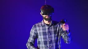 Το γενειοφόρο άτομο σε ένα διαλογικό κράνος εικονικής πραγματικότητας χορεύει και απολαμβάνει την εικονική πραγματικότητα με τους απόθεμα βίντεο