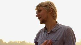 Το γενειοφόρο άτομο στέκεται και βάζει την τρίχα στη διαταγή στο riverbank στο ηλιοβασίλεμα στην slo-Mo απόθεμα βίντεο
