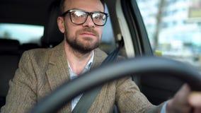 Το γενειοφόρο άτομο στα γυαλιά οδηγεί ένα αυτοκίνητο και την κραυγή σε κάποιο κοντά σε τον ή το εξωτερικό απόθεμα βίντεο
