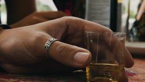 Το γενειοφόρο άτομο στα ποτήρια πίνει το κονιάκ στο πεζούλι αλκοολών Κοντό γυαλί ευθυμία απόθεμα βίντεο