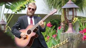 Το γενειοφόρο άτομο στο μαύρο κοστούμι παίζει την κιθάρα ενεργά και βγαίνει φιλμ μικρού μήκους