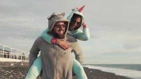 Το γενειοφόρο άτομο συνεχίζει πίσω την εύθυμη φίλη της, που περπατά πέρα από την παραλία φιλμ μικρού μήκους