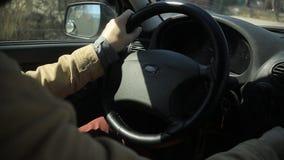 Το γενειοφόρο άτομο τρόπου ζωής οδηγά ένα αυτοκίνητο, κρατώντας το τιμόνι με τα χέρια του απόθεμα βίντεο