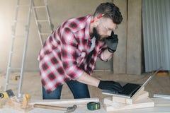 Το γενειοφόρο άτομο Hipster είναι ξυλουργός, οικοδόμος, στάσεις σχεδιαστών στο wo Στοκ Εικόνες