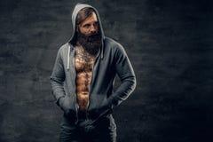 Το γενειοφόρο αρσενικό με τη δερματοστιξία σε ένα στήθος, έντυσε σε ένα γκρίζο hoodie Στοκ εικόνες με δικαίωμα ελεύθερης χρήσης