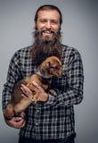 Το γενειοφόρο αρσενικό που ντύνεται σε ένα πουκάμισο καρό κρατά το σκυλί ασβών Στοκ φωτογραφία με δικαίωμα ελεύθερης χρήσης