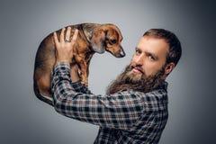 Το γενειοφόρο αρσενικό που ντύνεται σε ένα πουκάμισο καρό κρατά το σκυλί ασβών Στοκ εικόνες με δικαίωμα ελεύθερης χρήσης