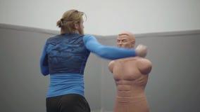 Το γενειοφόρο επαγγελματικό άτομο με το αθλητικό σώμα και ξανθός μακρυμάλλης κάνουν sidekick σε ένα μανεκέν κιβωτίων βαριδιών στη φιλμ μικρού μήκους