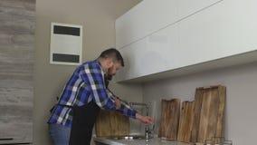 Το γενειοφόρο καυκάσιο άτομο στην ποδιά πλένει δικοί του παραδίδει τη σύγχρονη κουζίνα πρίν μαγειρεύει, υγιεινή, αργό MO απόθεμα βίντεο