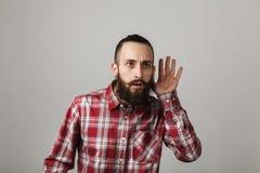 Το γενειοφόρο όμορφο άτομο ακούει στο κόκκινο τακτοποιημένο πουκάμισο στην γκρίζα ΤΣΕ στοκ φωτογραφίες
