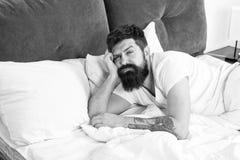 Το γενειοφόρο hipster ατόμων ξύπνησε πάρα πολύ νωρίς και αισθάνεται νυσταλέο και κουρασμένο Νωρίς για να σηκωθεί Σας κρατήστε παν στοκ εικόνες