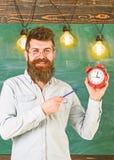 Το γενειοφόρο hipster κρατά το ρολόι, πίνακας κιμωλίας στο υπόβαθρο Άτομο με τη γενειάδα και mustache στο χαμόγελο των στάσεων πρ στοκ φωτογραφία