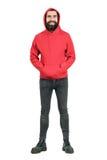 Το γενειοφόρο punker γέλιου που φορά το κόκκινο hoodie που εξετάζει τη κάμερα με παραδίδει τις τσέπες Στοκ φωτογραφία με δικαίωμα ελεύθερης χρήσης