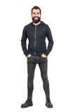 Το γενειοφόρο punker γέλιου στο μαύρο hoodie με παραδίδει τις τσέπες εξετάζοντας τη κάμερα Στοκ φωτογραφία με δικαίωμα ελεύθερης χρήσης
