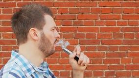 Το γενειοφόρο vaper καπνίζει ένα ηλεκτρονικό τσιγάρο και φυσά ένα σύννεφο του ατμού φιλμ μικρού μήκους