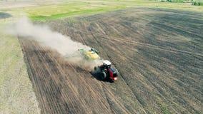 Το γεωργικό τρακτέρ σπέρνει το έδαφος σε ένα σύννεφο της σκόνης απόθεμα βίντεο