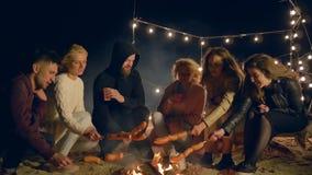Το γεύμα στην παραλία, φίλοι μαγειρεύει το γεύμα στην πυρά προσκόπων στην αμμώδη παραλία τη νύχτα στο φωτισμό λαμπτήρων απόθεμα βίντεο
